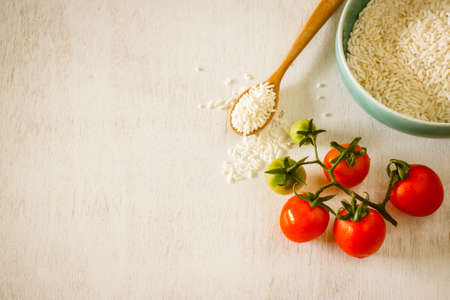 biologic: rice in blue cup with fresh tomato put on vintage white table