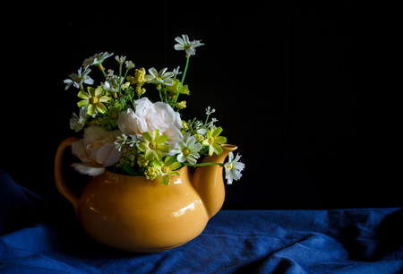 yellow tea pot: Flower in a yellow tea pot and vintage cup of coffee,cozy home rustic decor, cottage living, still life image dark tone