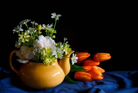 yellow tea pot: Flower in a yellow tea pot and orange tulip,cozy home rustic decor, cottage living, still life image dark tone Stock Photo