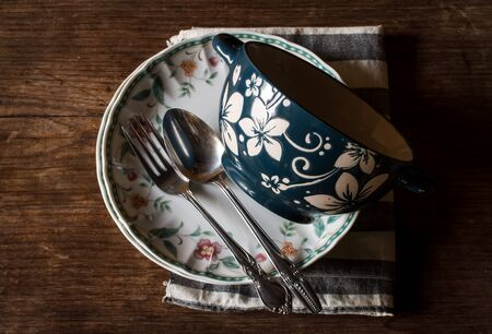 pewter: Antique decorative dinner plate and vintage pewter fork on distressed wood with decorative carved border.Still life image dark tone Stock Photo