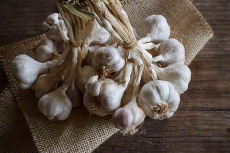 preventative: Bunch of garlic put on old wood image dark tone
