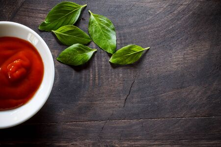 provocative food: plate of tomato sauce with organic basil put on black old wooden Stock Photo