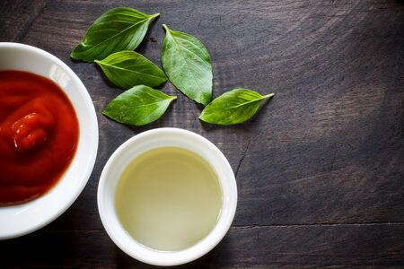 sauces: Assorted Sauces prepare for cooking in small plate with basil put on black old wooden