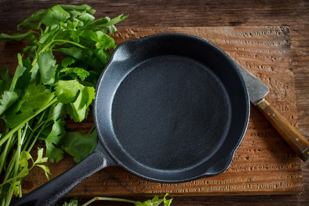 Vintage cast iron skillet on rustic wood background with vegetable prepare for cook