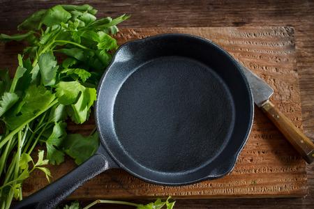 utensilios de cocina: Vintage sartén de hierro fundido en el fondo de madera rústica con vegetales prepararse para cocinero Foto de archivo