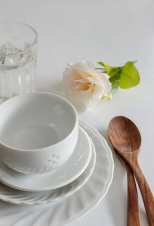 antique dishes: Vintage table setting with roses, antique rustic dishes and cutlery on the wooden background