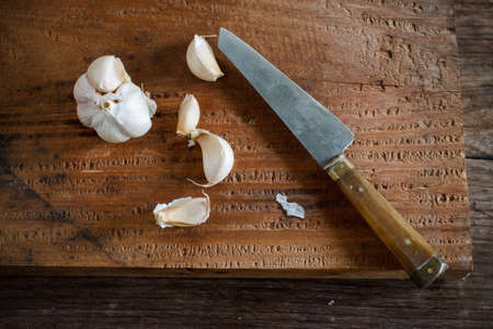 preventative: organic garlic with knife put on wooden board Stock Photo