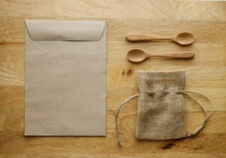 paper craft: Burlap bag and paper bag with wooden spoon set. Object put on surface wood table. Image retro filter effect. Brown tone.