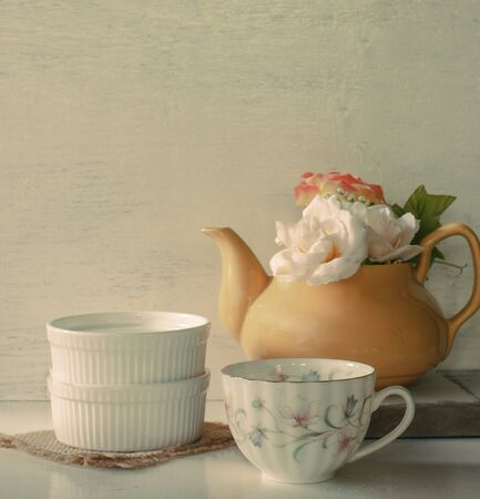 yellow tea pot: Flower in a yellow tea pot and vintage cup of coffee on wooden background, cozy home rustic decor, cottage living. Image soft tone.