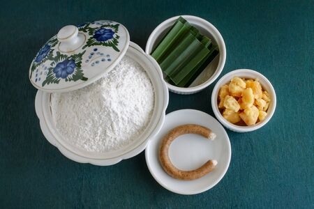 sweetmeats: Ingredient for Thai dessert. flour, palm sugar, pandan leaf, candle used for smoking sweetmeats. object put on green wooden background.
