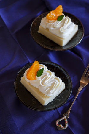 small cake: small cake with butter cream and fresh mandarin orange served in black plate.