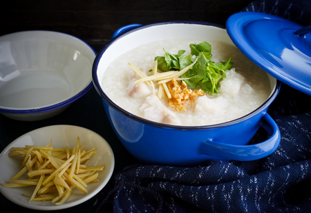 asian food: Local cuisine of Asia  : porridge rice gruel with fish served in blue bowl, congee. Still life image dark tone.