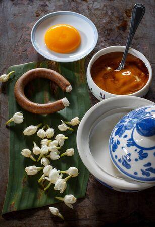 sweetmeats: Egg yolk, coconut milk, palm sugar, Thai jasmine, candle used for smoking sweetmeats put on banana leaf. still life image dark tone.