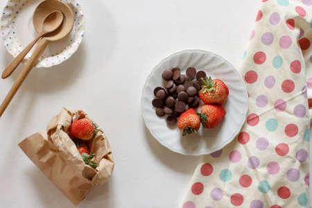 fresh strawberry , dark chocolate chip with fresh milk in bottle put on polka dot cloth background.