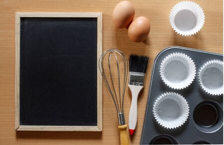 recipe background: Blackboard for recipe of cake on brown wood background, cupcake ingredient. Flat lay of ingredient of cake.