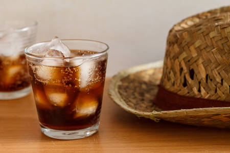 carbonation: glass of cola with iced cube and hat on summer time.