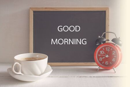 second breakfast: cup of black coffee with red vintage alarm clock and blackboard on wooden background Stock Photo