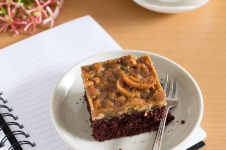 small plate: sweet chocolate cake with nuts caramel served in small plate. Stock Photo