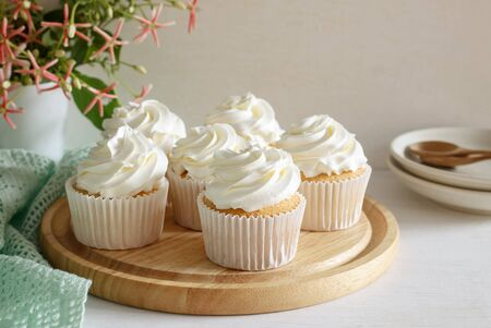 sweet vanilla cupcake with buttercream put on wooden board, image soft tone. Stock Photo
