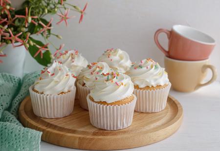 vanilla cupcake: sweet vanilla cupcake with buttercream put on wooden board, image soft tone. Stock Photo