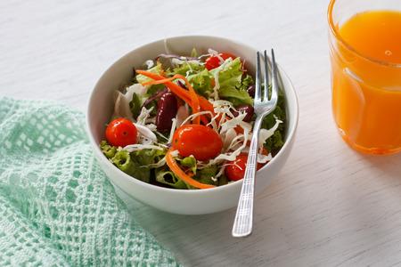 comida rica: ensalada fresca con tomates cherry, frijoles rojos y zanahoria servido con jugo de una naranja en la mesa de madera blanca. Foto de archivo