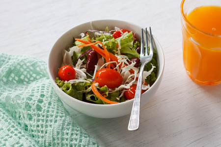 good food: fresh salad with cherry tomatoes, red beans and carrot served with orange juice put on white wood table.
