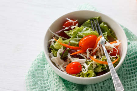 plato del buen comer: ensalada fresca con tomates cherry, frijoles rojos y zanahoria servido en un tazón blanco puso en la mesa de madera blanca.