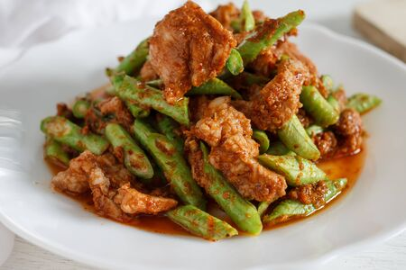 long bean: Authentic local Thai food: Red curry pork with yard long bean serve on white dish. Stock Photo