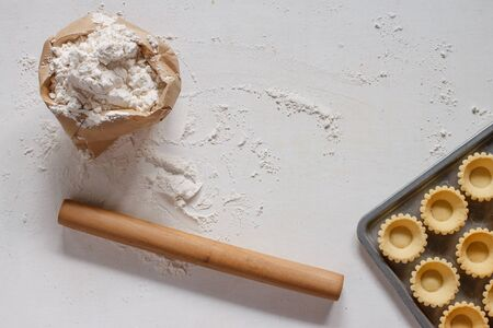 Homemade tart shell , flour in paper bag and rolling pin on white wood table.