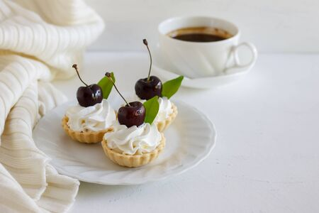 Delicious cherry tart with whipping cream and black coffee on white background. Stock Photo