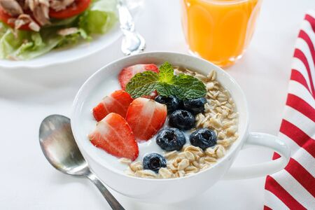 Yogurt with oat flake and fresh berries for healthy morning meal put on white wood background, Breakfast set.