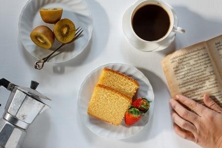 Delicious pound cake, kiwi, strawberry and espresso coffee put on white wood background. Stock Photo