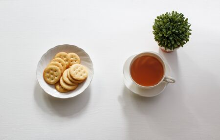 a cup of English tea with salt cracker on white table. Stock Photo