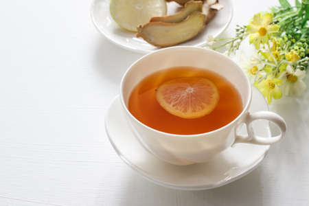 cup of tea with lemon and ginger on white table.