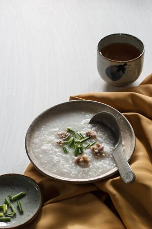 Rice porridge with pork put on white wooden table, rustic food. Stock Photo