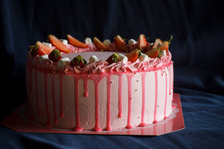 Delicious Pink buttercream cake top with fresh strawberry and marshmallow put on blue cloth background.