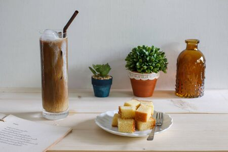 Glass of cold iced coffee served with pound cake put on wood background