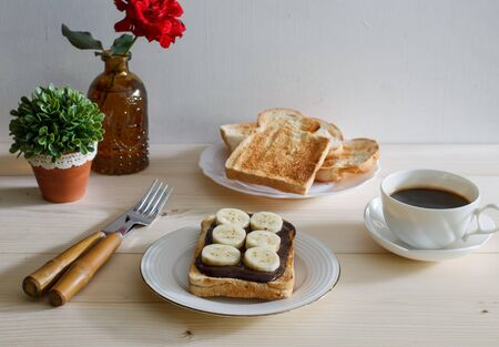chocolate and peanut buttered toasts with pieces of bananas on a plate with cup of espresso coffee.