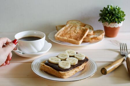 chocolate and peanut buttered toasts with pieces of bananas on a plate, woman hand catch cup of espresso coffee Stock Photo
