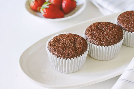Chocolate cupcakes on white plate and fresh strawberry. Stock Photo
