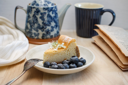 Homemade New York cheesecake with fresh blueberry, cozy blanket white color and old tea pot, Breakfast set in holiday in winter. Stock Photo