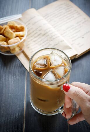 Iced coffee with milk, old book, cracker on wood.