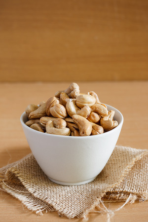 cashew nut in a white bowl with sackcloth. Stock Photo
