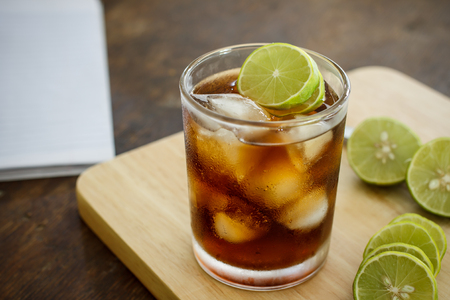 cola in glass with lime and ice on wood table Stock Photo
