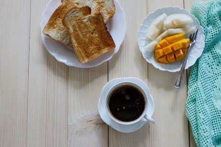 black coffee with toast bread and fruit.