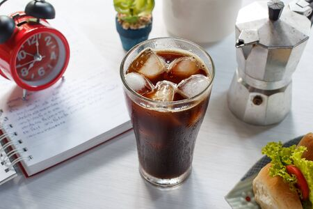 Glass of cold iced coffee with sandwich.