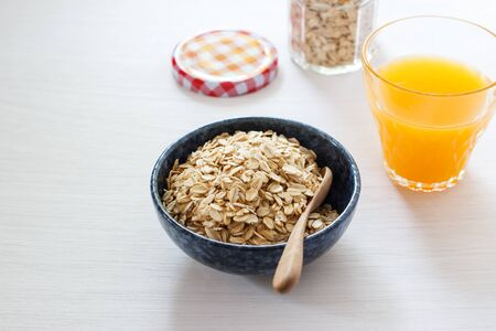 Rolled oats or oat flakes with orange juice, healthy breakfast set on white table.