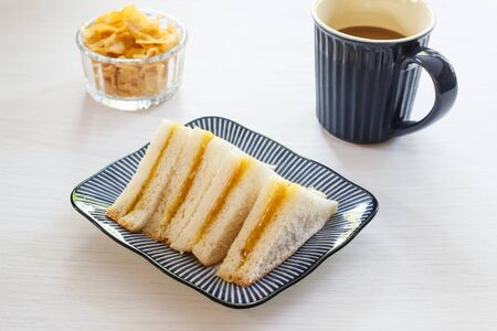 delicious sandwich with black coffee in blue cup.