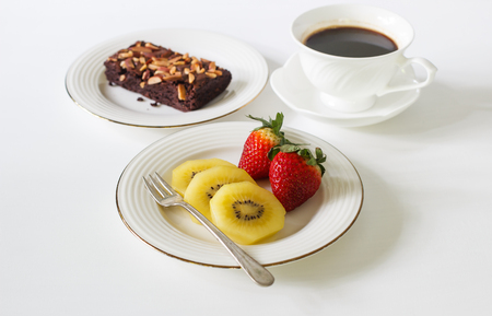 Fresh fruit kiwi, strawberry, black coffee and chocolate brownie on white table. Stock Photo
