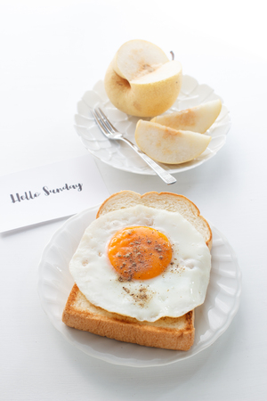 fried egg on toast, fruit and text